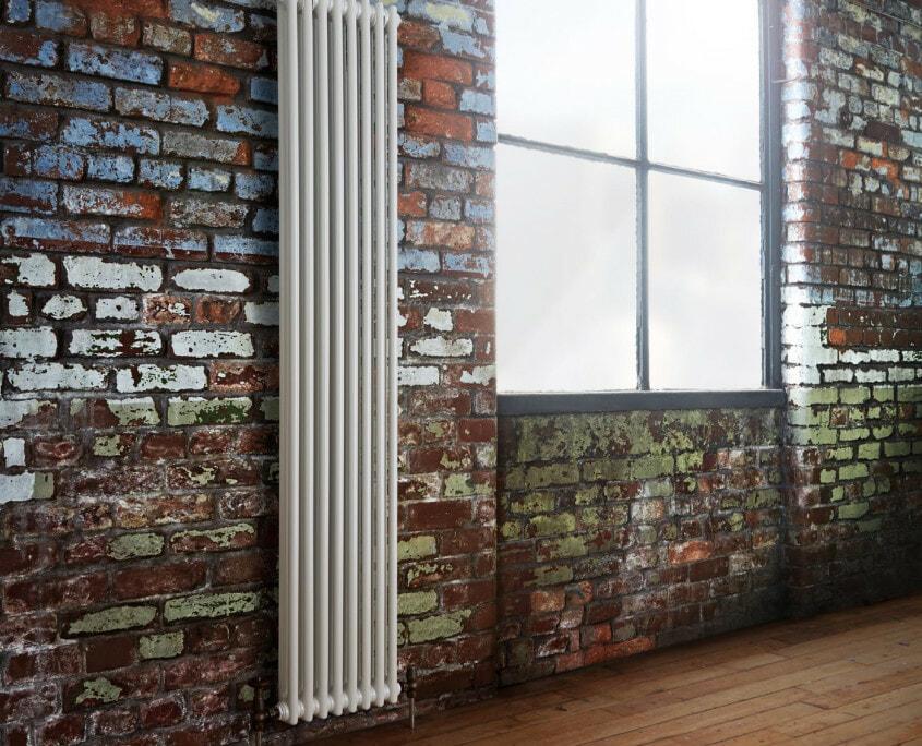 white radiator on brick wall